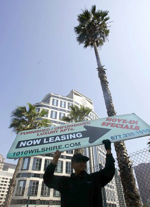 Sign twirler Santos Pastor advertises apartments on Wilshire Boulevard in downtown Los Angeles.